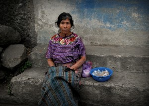 An indigenous woman sells dulces on the side of the road.