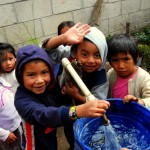 The local kids, on break from class, come to play and help fill buckets of water.