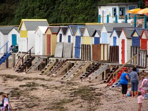 Beach huts and cafe at Corbyn's Beach. Photo via Wikimedia, by David Dixon