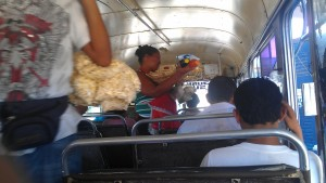 Vendors sell bags of popcorn and other snacks on a Chicken Bus.