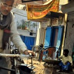 A Delhi man rides a bike past a vendor, cooking in front of his shop.