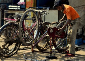 A boy fixes bikes outside his shop